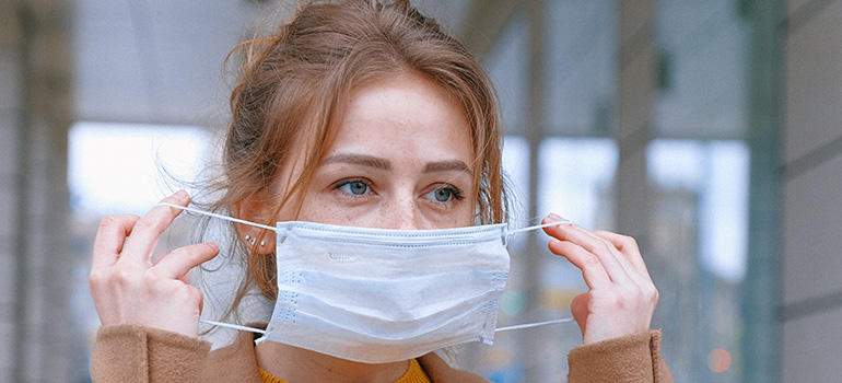woman putting on a mask when moving during the coronavirus outbreak
