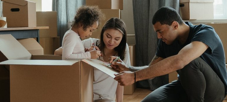 A whole family packing moving boxes together