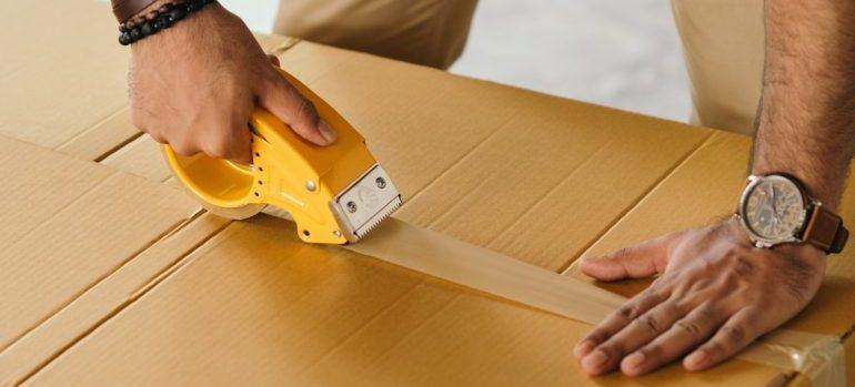 man sealing storage box