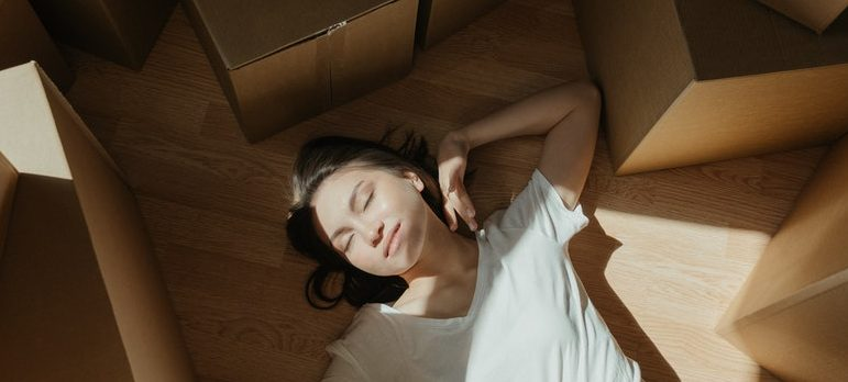 A woman sleeping among many cardboard moving boxes