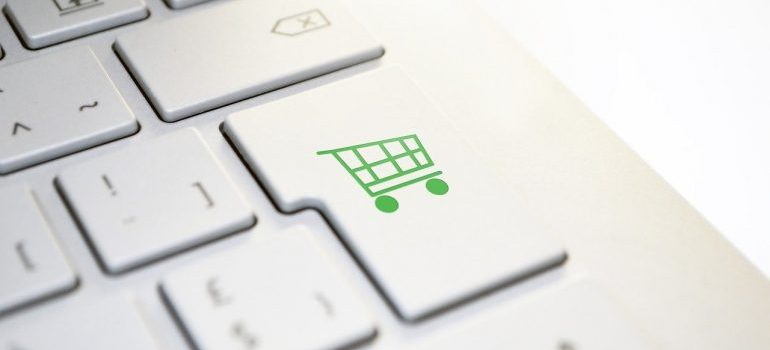 A green shopping cart on a white keyboard.