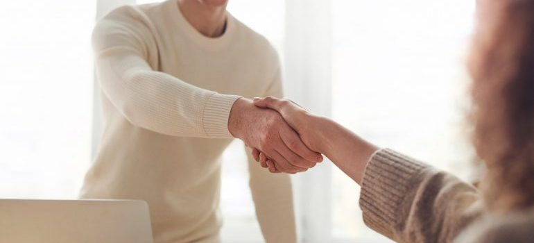 woman handshaking with a person from moving company