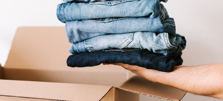 Person packing clothes for moving