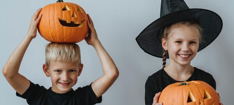 Siblings holding carved Halloween pumpkins