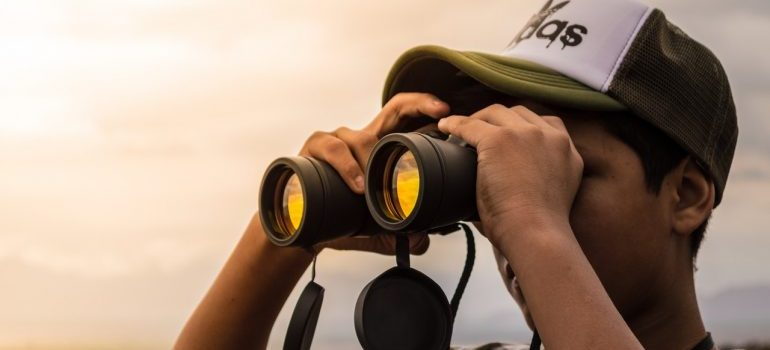 man with binoculars representing the search for trustworthy Ottawa movers