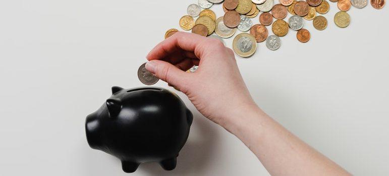 A person placing a coin inside a piggy bank
