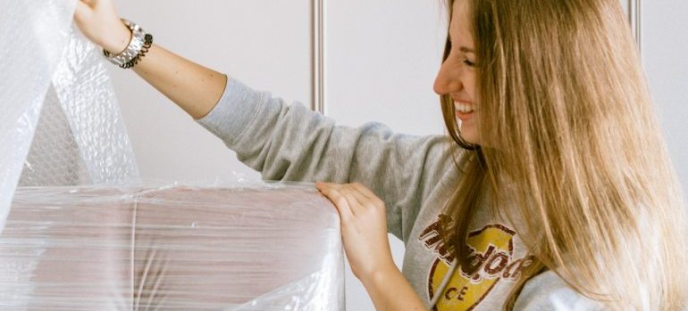 woman protecting furniture with plastic wrap