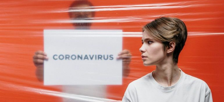 woman with coronavirus sign behind her