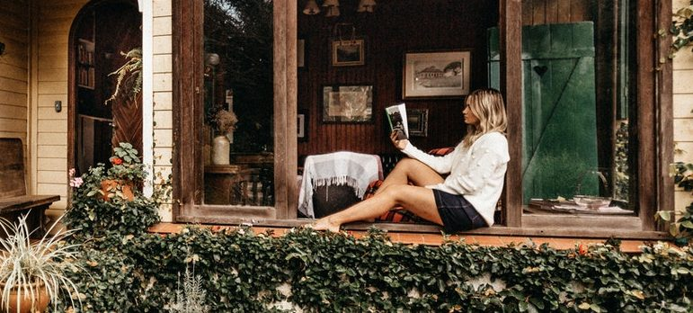 A woman sitting and reading on the porch