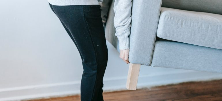 woman moving couch by herself