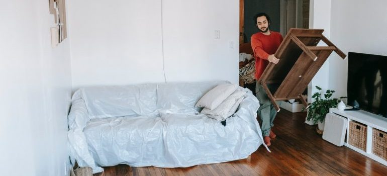 man moving furniture around his apartment