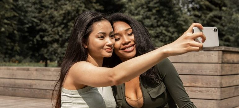 two female friends taking a selfie in the park