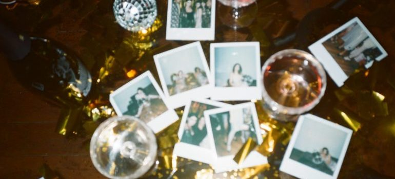 Polaroid pictures next to the glasses on the table.