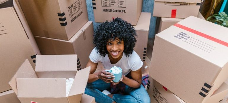A smiling woman among moving boxes, waiting for small movers Ottawa.