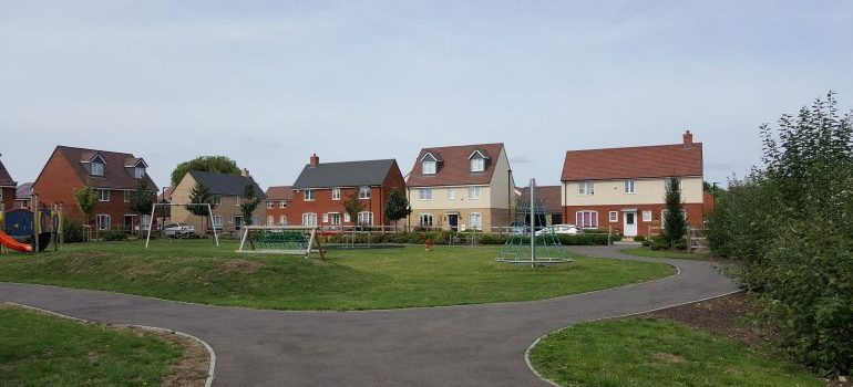 a green surface in front of a few houses