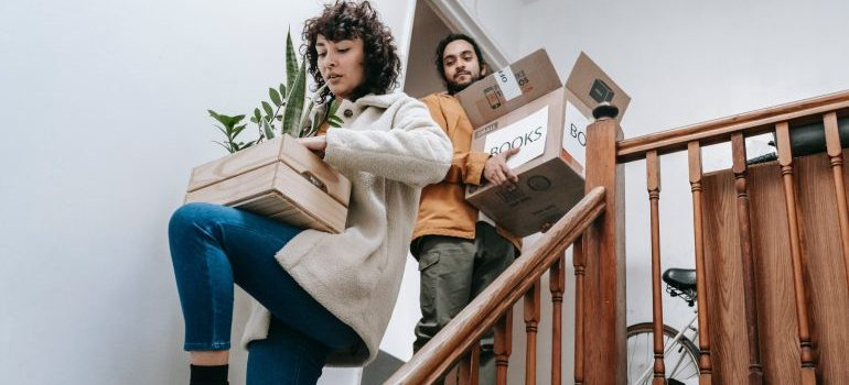 Couple moving cardboard boxes.