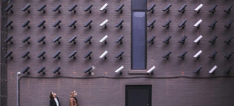 Two persons looking at a wall of security cameras.