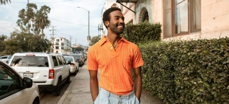 A smiling man in orange shirt