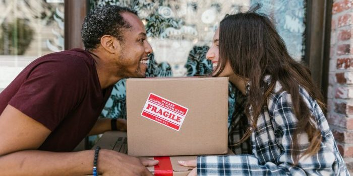 A woman and a man holding a box