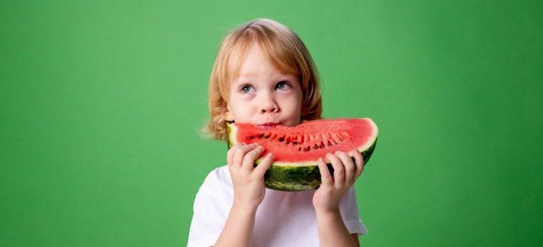 Kid eating a watermelon