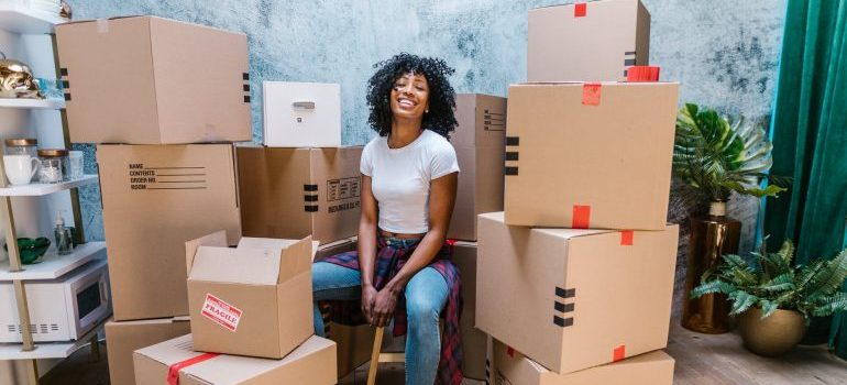 woman sitting between packing boxes