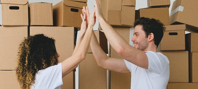 two people packing for moving as a symbol of how to stay efficient while unpacking