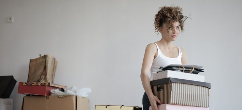 A woman carrying boxes decluttering to speed up her relocation to Carleton Place